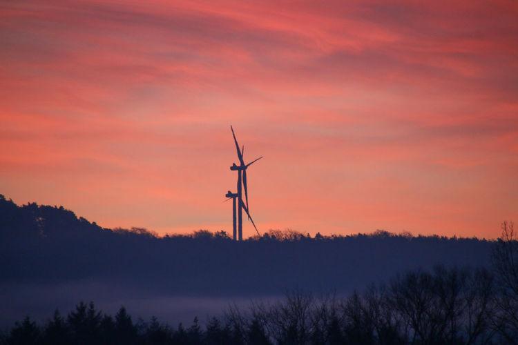 Silhouette wind turbines on landscape against romantic sky at sunset