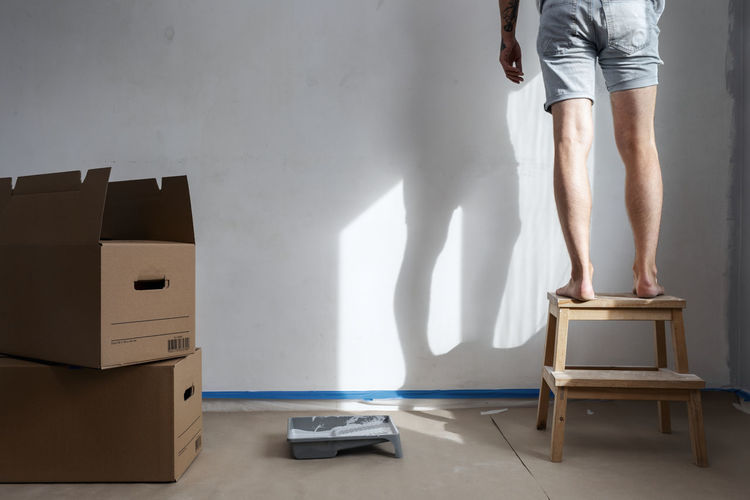 Low section of woman standing on floor at home