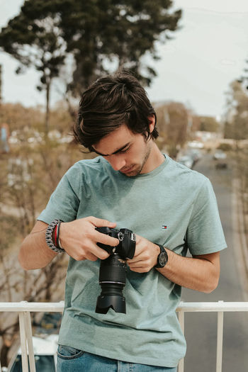 Young man photographing with camera