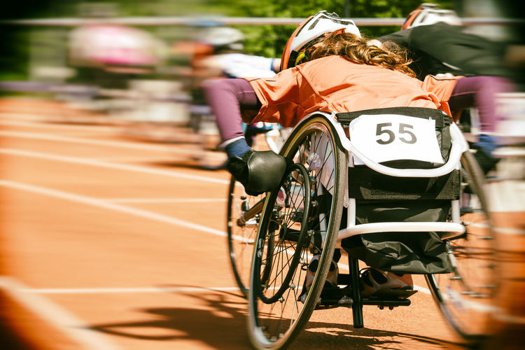Rear view of people racing in wheelchairs