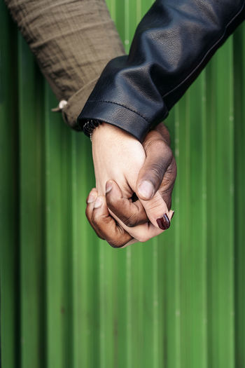 Cropped image of couple holding hands against green corrugated iron