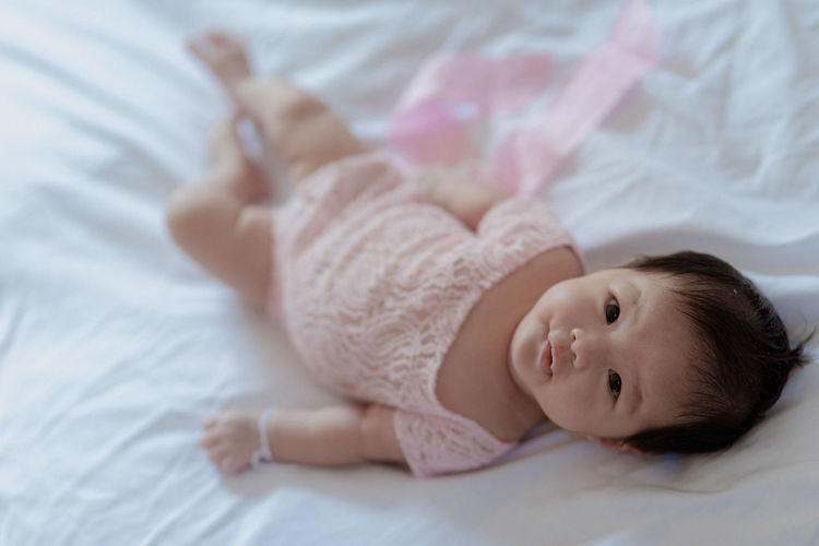 High angle portrait of baby girl lying on bed at home