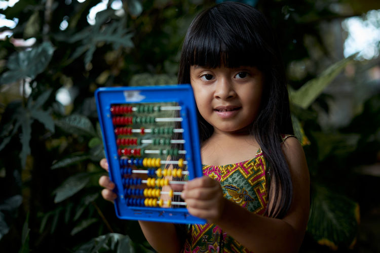 Close-up of girl playing with abacus against plants