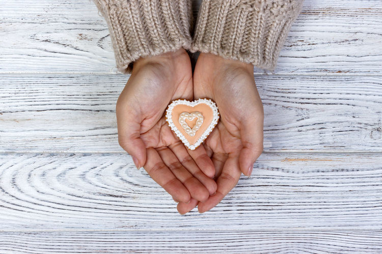Directly above shot of copped hands holding heart shape cookie