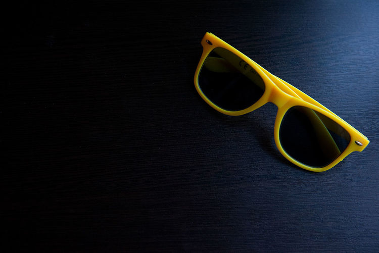 High angle view of yellow sunglasses on wooden table
