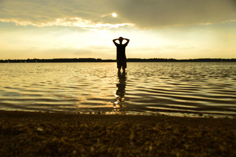 Beauty In Nature Day Full Length Lake Leisure Activity Lifestyles Men Nature One Person Outdoors People Real People Reflection Scenics Silhouette Sky Standing Sunset Tranquil Scene Tranquility Water