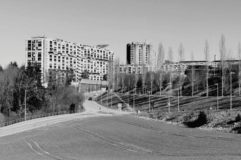 Road by buildings against clear sky