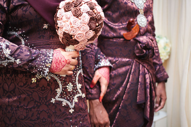 Midsection of bride holding bouquet standing with groom during wedding