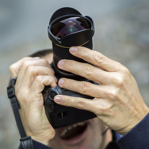 Low angle view of man photographing while standing outdoors