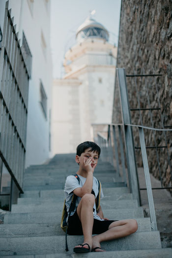 Boy sitting on staircase against building