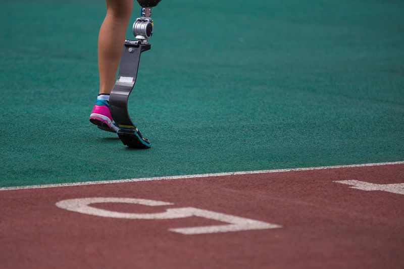Low Section Of Woman With Artificial Leg Running On Track