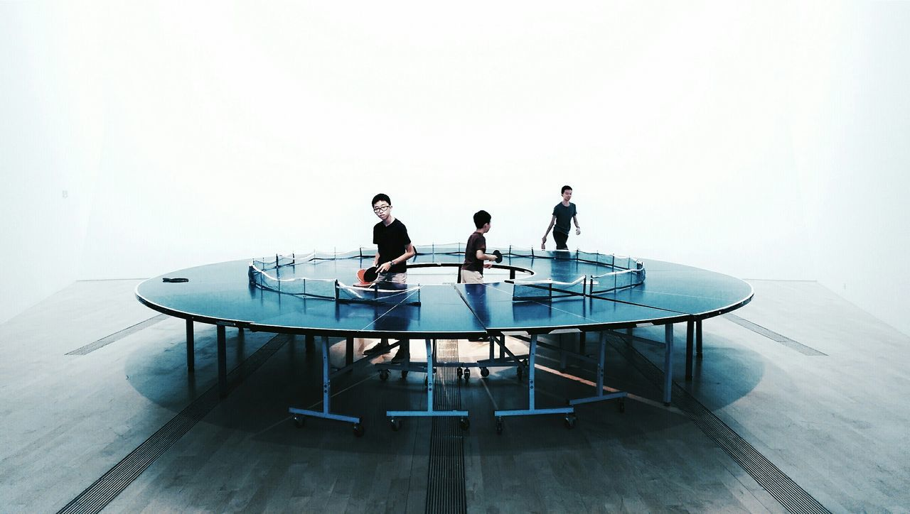 Boys playing ping pong go-round against white background