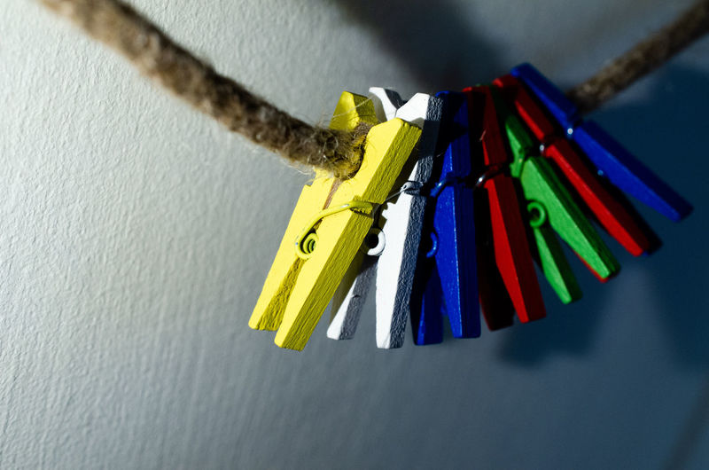 Close-up of multi colored hanging on rope against wall