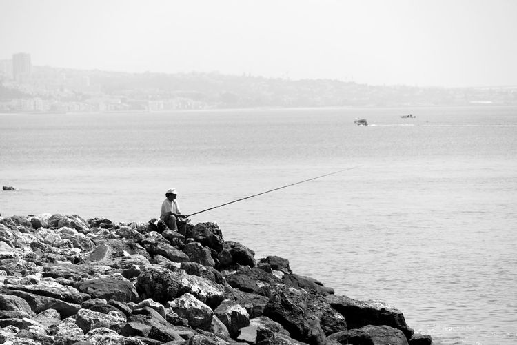 LONELY FISHERMAN ON THE SHORE