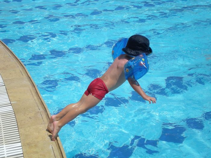 Rear View Of Diving Into Swimming Pool