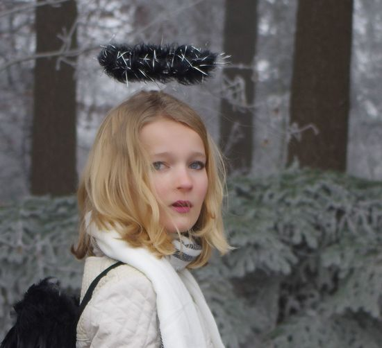 Young Woman Wearing Costume Wing And Halo At Forest During Winter