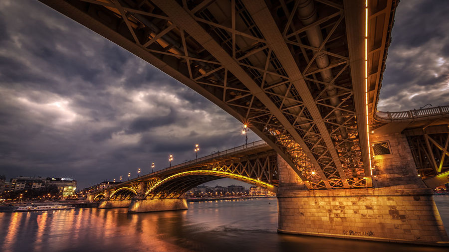 Low angle view of illuminated bridge against cloudy sky