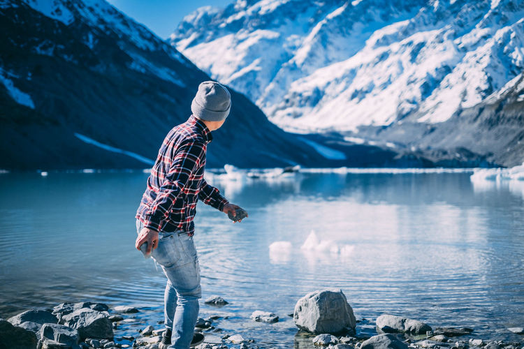 Man standing on rock by lake against snowcapped mountains during winter