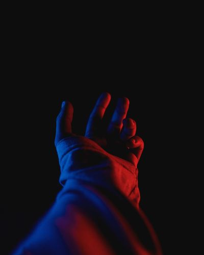 Close-up of hands against black background