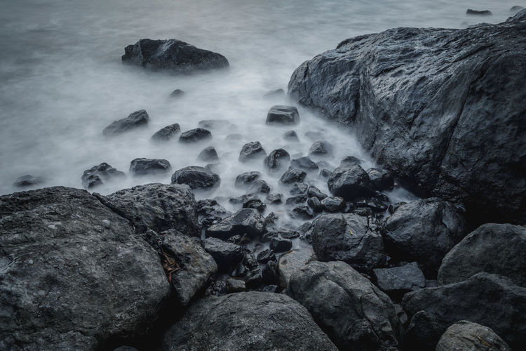 Rocks by the sea with milky seas Coast Desaturated Grey Hard Rock Sea Slow Shutter Stone Water Wet