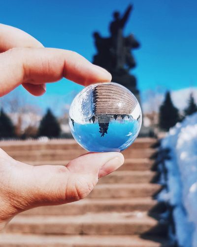 Midsection of person holding crystal ball against statue at temple