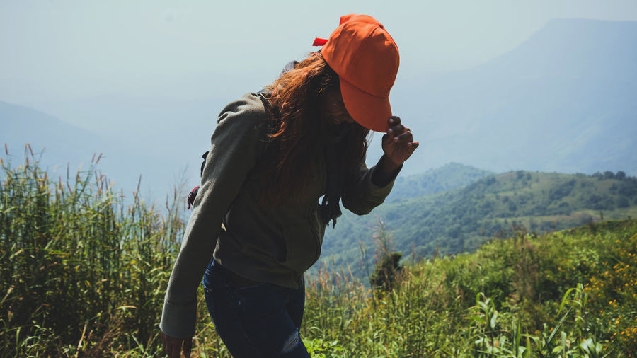 Woman looking down while standing against mountains against sky