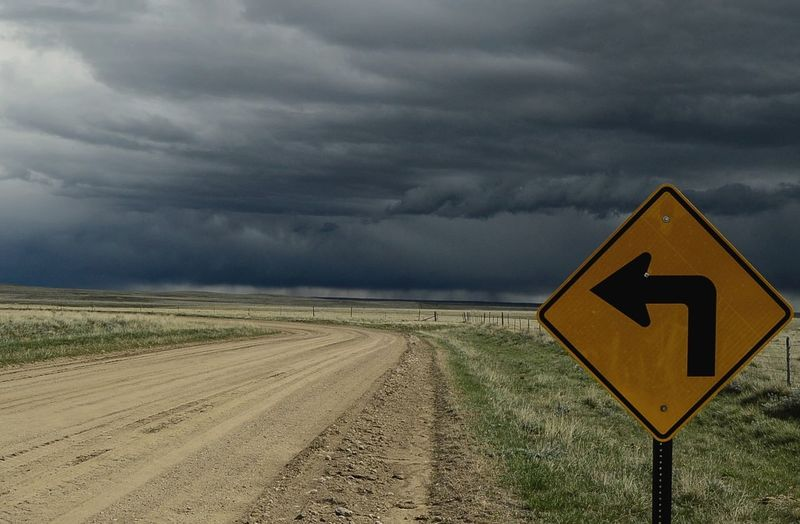 Sign out in middle of nowhere County Roade Day East Of Van Tassle Wyoming Landscape No People On Border Of Wyoming And Nebraska Outdoors Road Road Sign Rural Scene Storm Clouds West Of Harrrison Nebraska