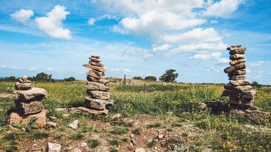 Stone stack on field against sky