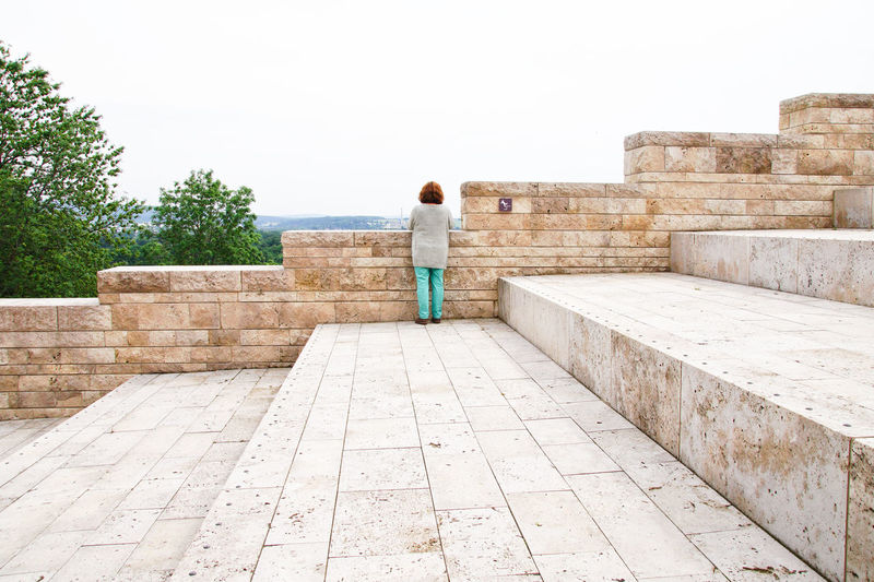 Rear view of woman standing on steps against clear sky