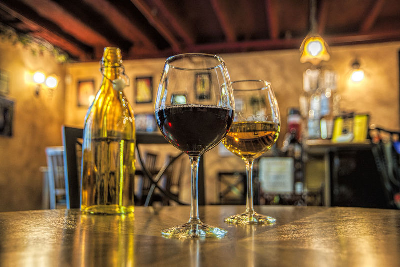 Wineglasses And Bottle On Table In Illuminated Cafe