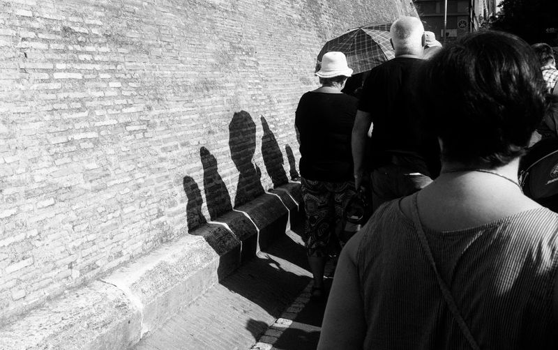 Rear view of people walking by wall