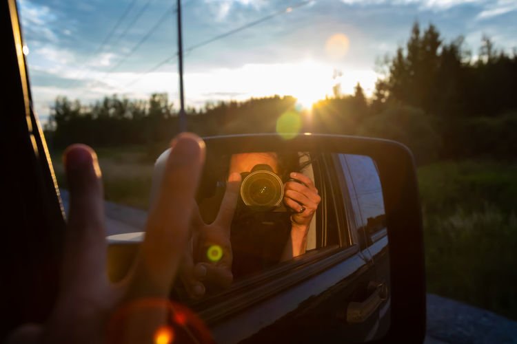 Woman photographing through car window
