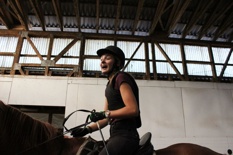 Low Angle View Of Happy Female Jockey Riding Horse At Stable