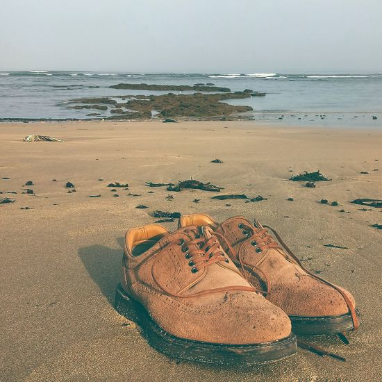 Close-up of shoes on beach against sky