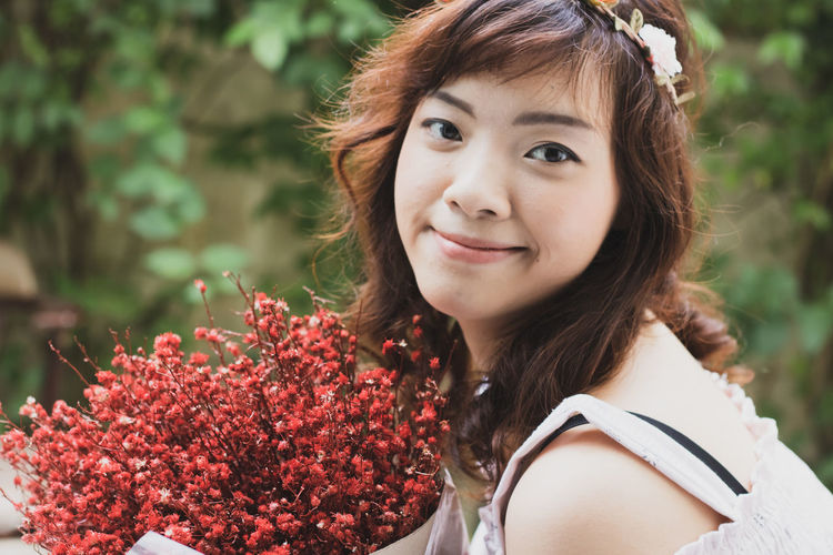 Close-up portrait of smiling woman with red flowering plants