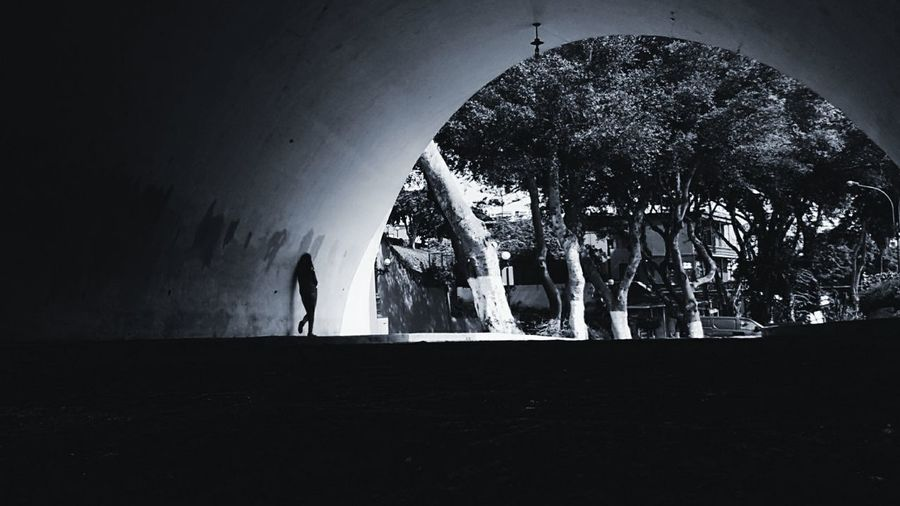 Silhouette people standing in tunnel
