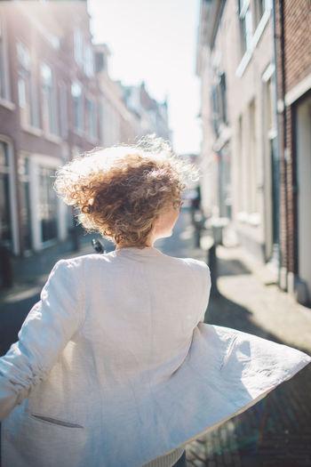 Happy woman walking on street in city