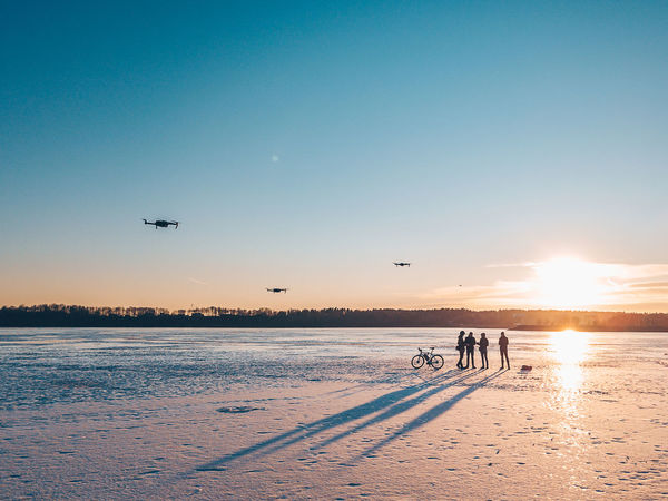 Man with drones Drones Ice Silhouettes Aerial View Air Vehicle Airplane Beauty In Nature Clear Sky Cold Temperature Flight Flying Frozen Water Group Of People Land Mavic Mavic Pro Mid-air Mode Of Transportation Nature Outdoors Real People Scenics - Nature Shadows Sky Snow Sun Sunlight Sunset Transportation Travel Water Winter