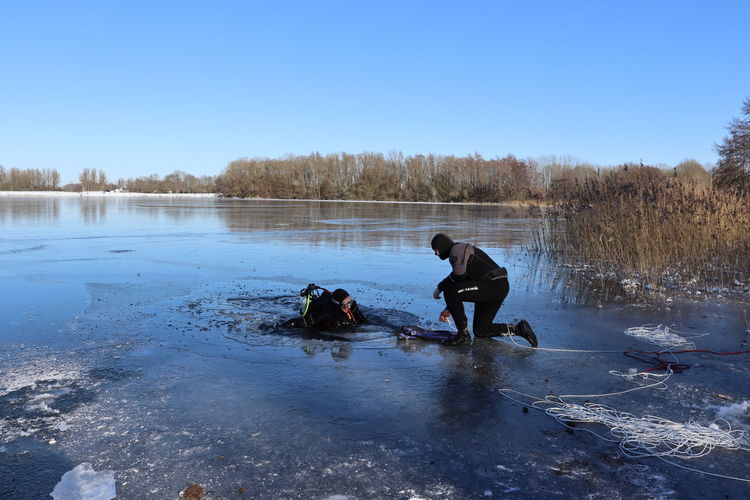 Men in lake against sky during winter
