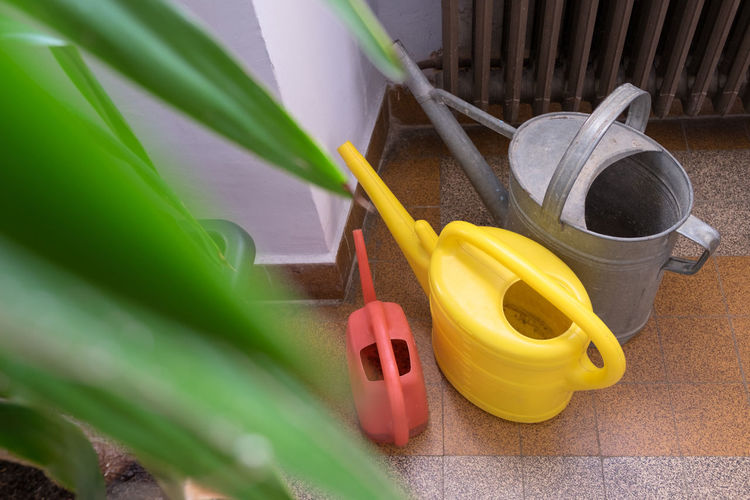 Collection of water cans in plastic and metal with plant and vintage radiator EyeEmNewHere Plant Watering Plants Bucket Close-up Day High Angle View Indoors  Leaf Metal No People Plastic Radiator Silver  Watering Watering Can Watering Cans Work Tool Yellow