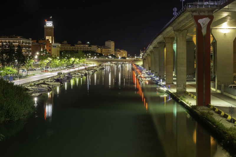 Illuminated bridge over canal amidst buildings in city at night