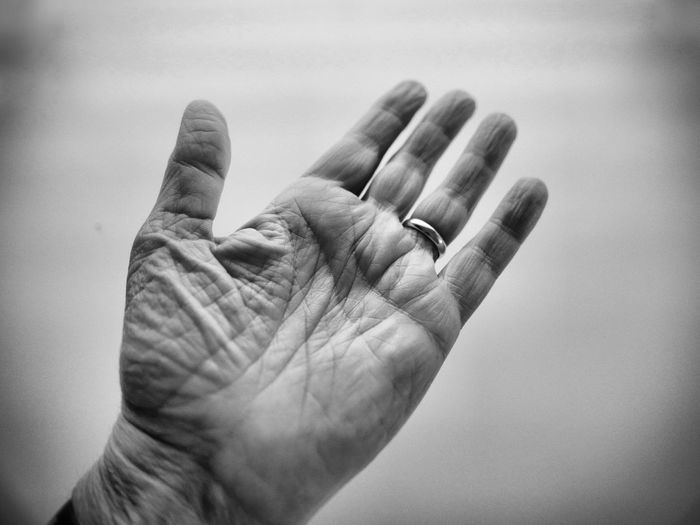 Close-up of wrinkled hand against white background