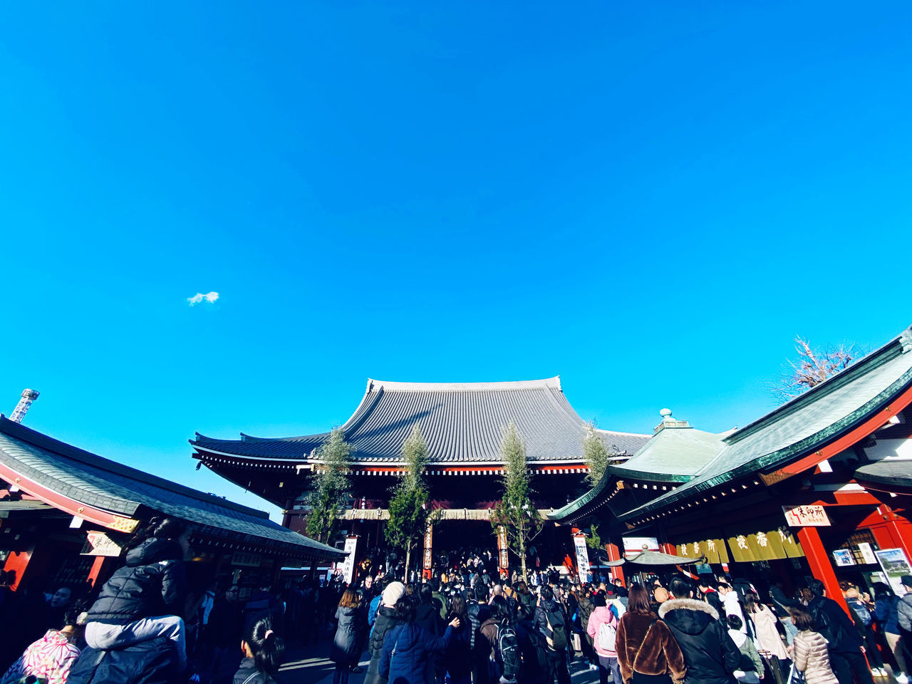 GROUP OF PEOPLE IN TEMPLE AGAINST BLUE SKY