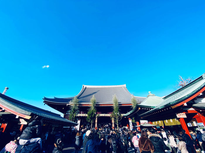 People at temple against clear blue sky