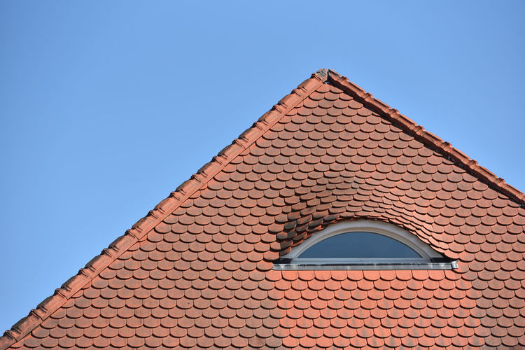 Low angle view of building tiles roof against clear blue sky