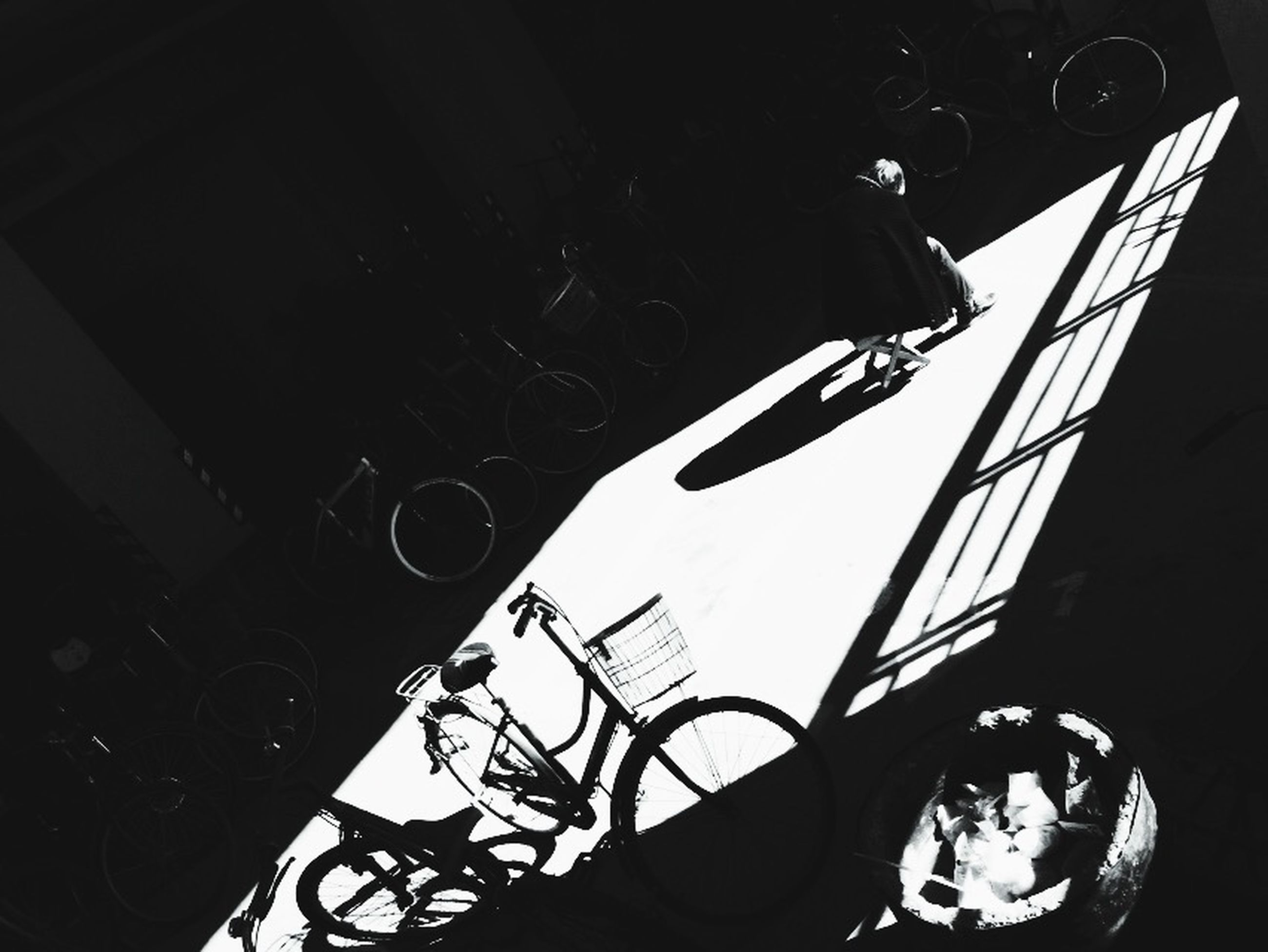 bicycle, low angle view, built structure, land vehicle, transportation, indoors, architecture, lighting equipment, shadow, sunlight, mode of transport, high angle view, illuminated, no people, night, parking, technology, building exterior, stationary