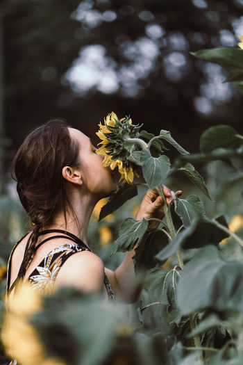 Young european woman with braided hair in a floral dress smelling on a sunflower in a field.
