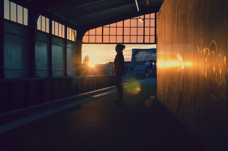 Silhouette man standing by window against orange sky