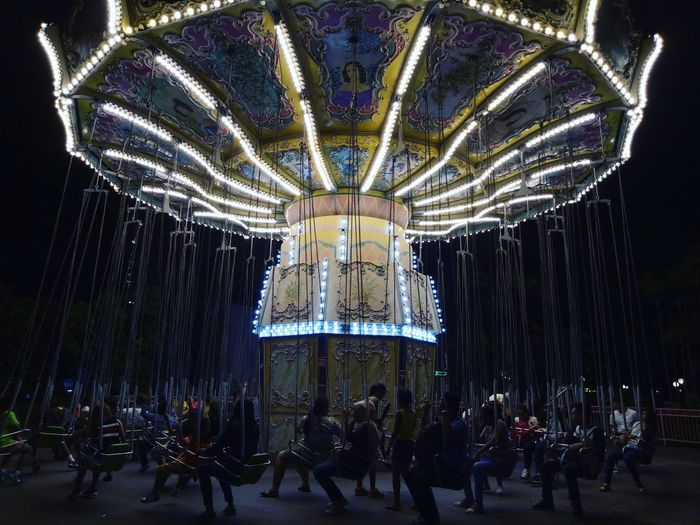 Illuminated Chain Swing Ride In Amusement Park At Night
