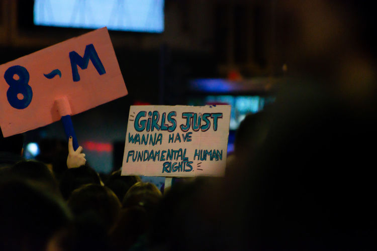 People holding placards with text during protest at night